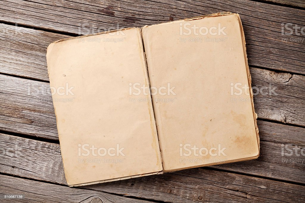 Open vintage book on wood stock photo