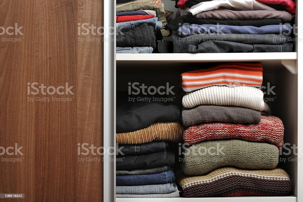 Open wardrobe with lots of folded clothes royalty-free stock photo