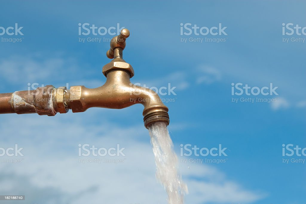 Open water faucet against a blue sky royalty-free stock photo