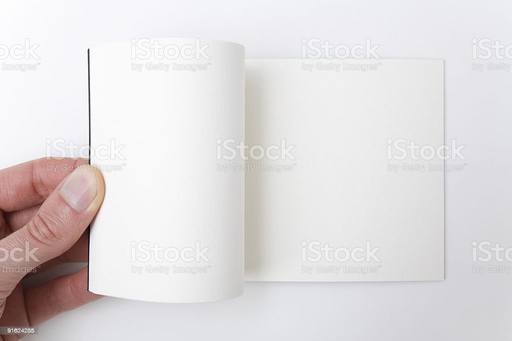 Open white book - A hand flipping pages. stock photo