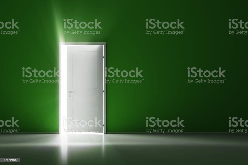 Open white door on green wall stock photo