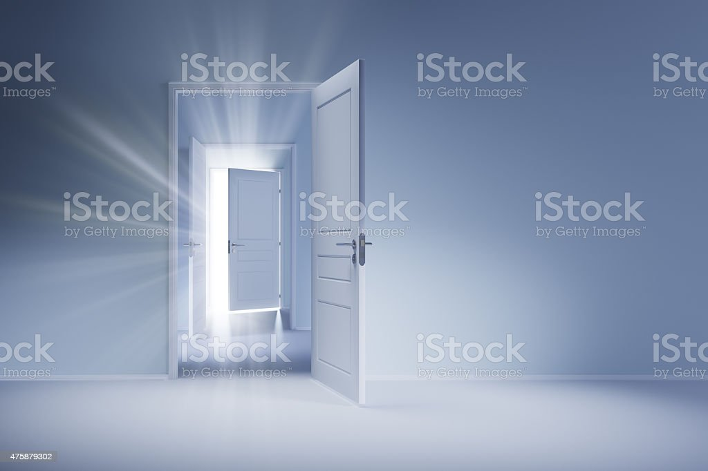 Open white doors with rays of light on blue wall stock photo