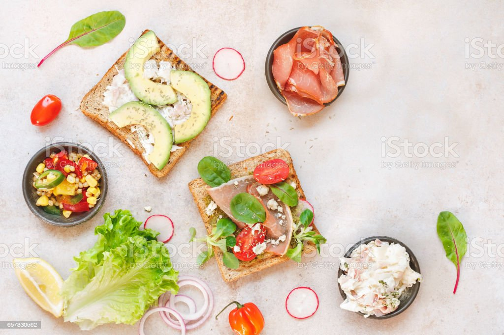 Open wholemeal sandwiches and various ingredients stock photo