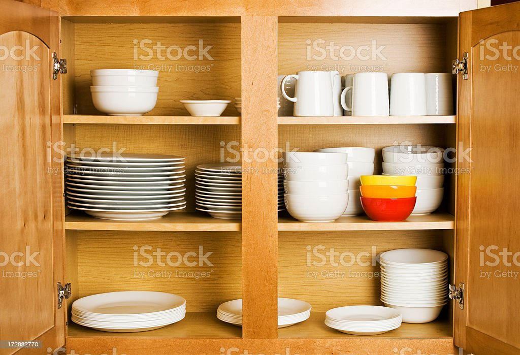 Open wood cupboard shelving plates dishes and jugs stock photo