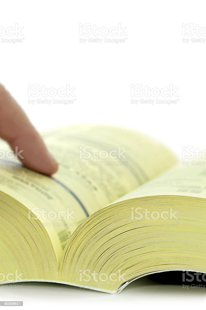 Open yellow pages with finger pointing stock photo
