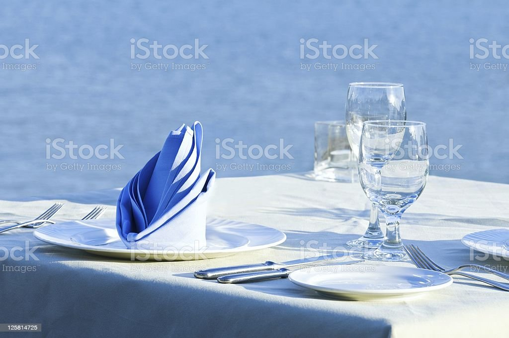 Open-air table setting for meals with elegant dishware royalty-free stock photo