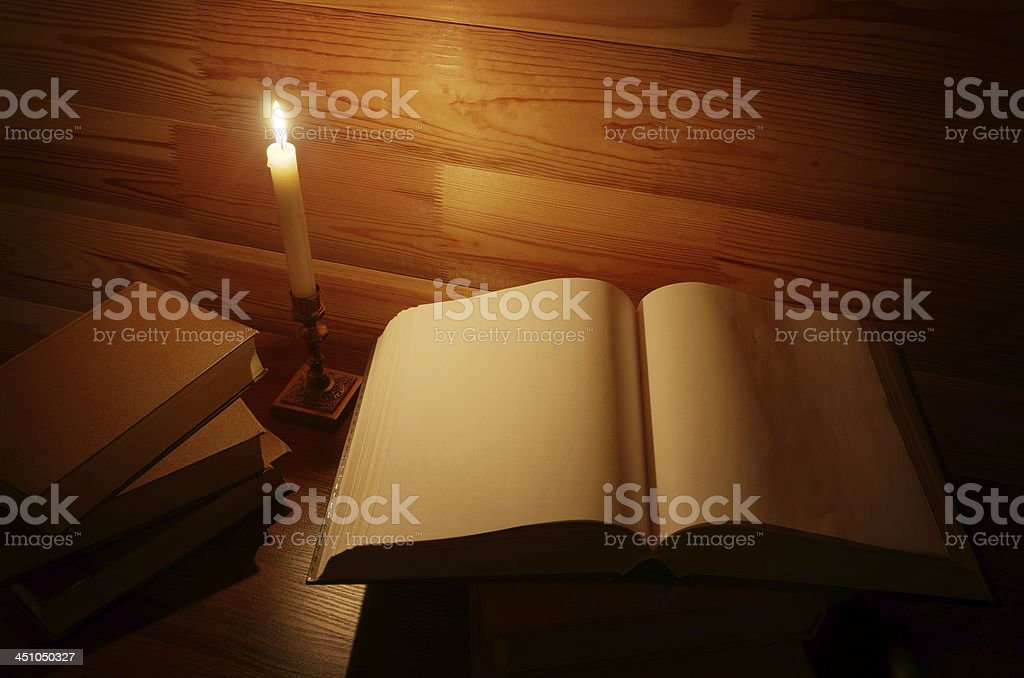 opened anciend book illuninated with burning candle stock photo