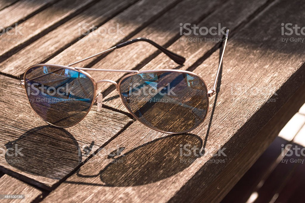 Opened and Standing Aviator Sunglasses on Table stock photo