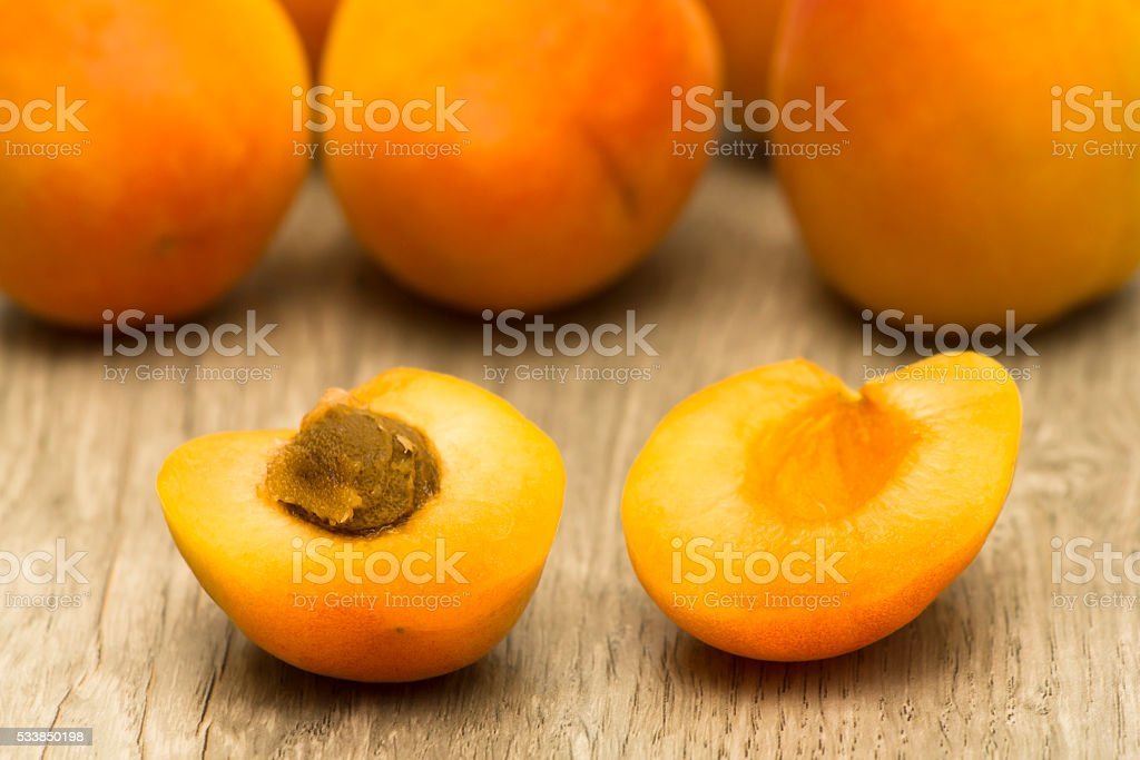 Opened apricot with seed inside on wooden textured table stock photo