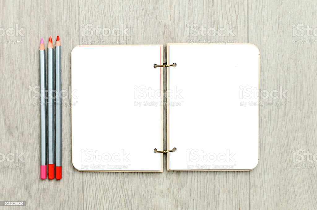 Opened blank notepad with colorful pencils on wooden table stock photo