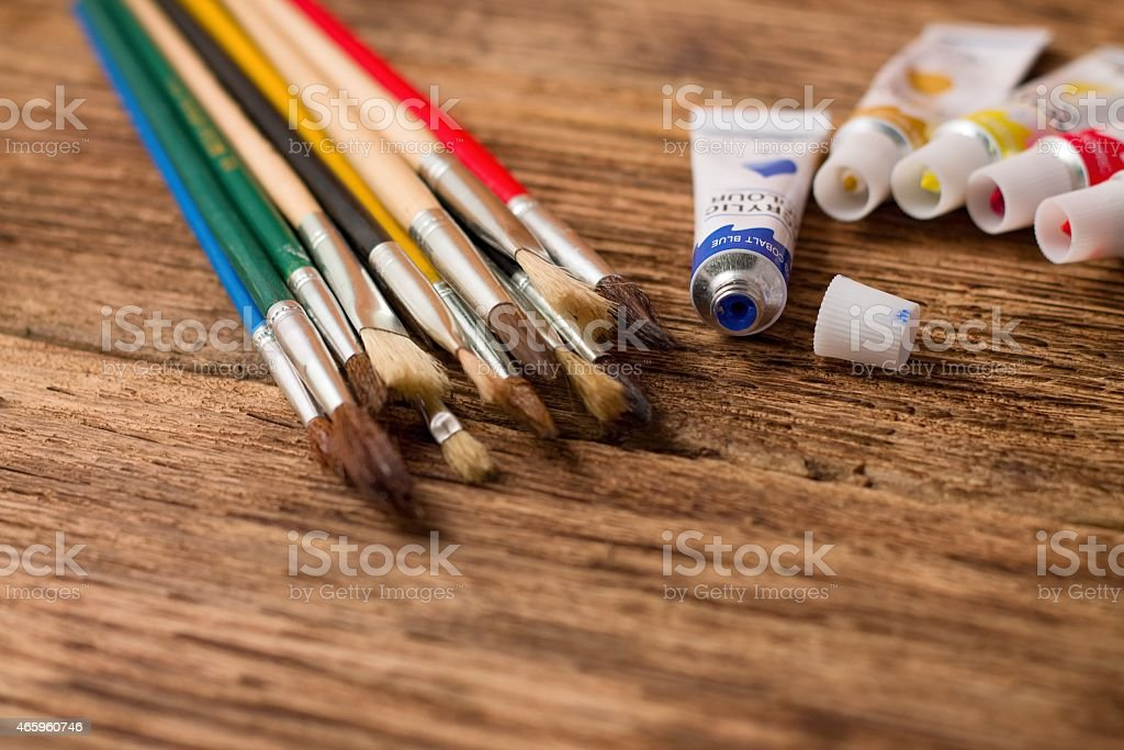 Opened blue acrylic color and set of paintbrushes stock photo