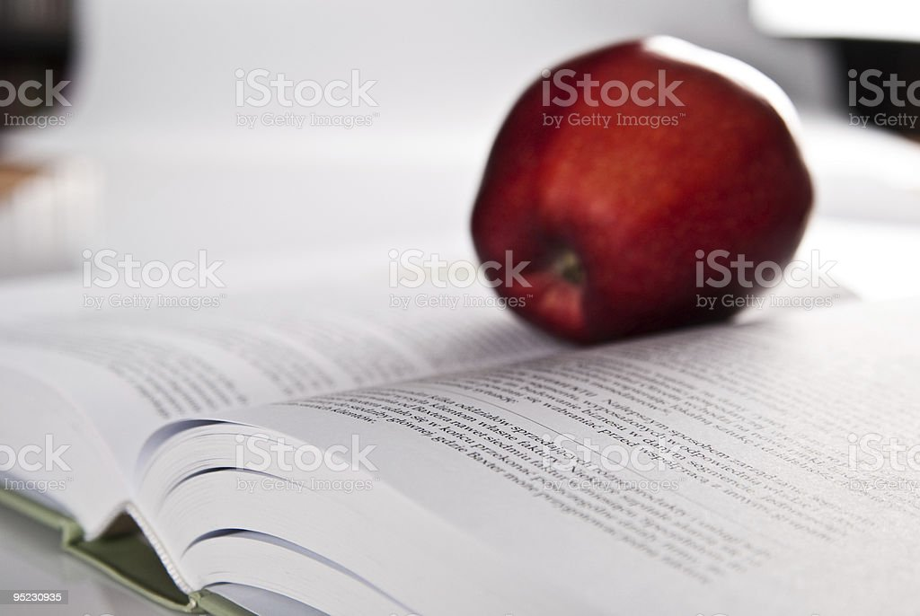 opened book and red apple royalty-free stock photo
