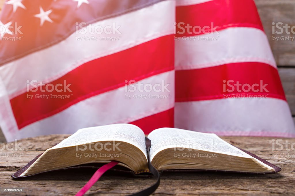 Opened book and USA flag. stock photo