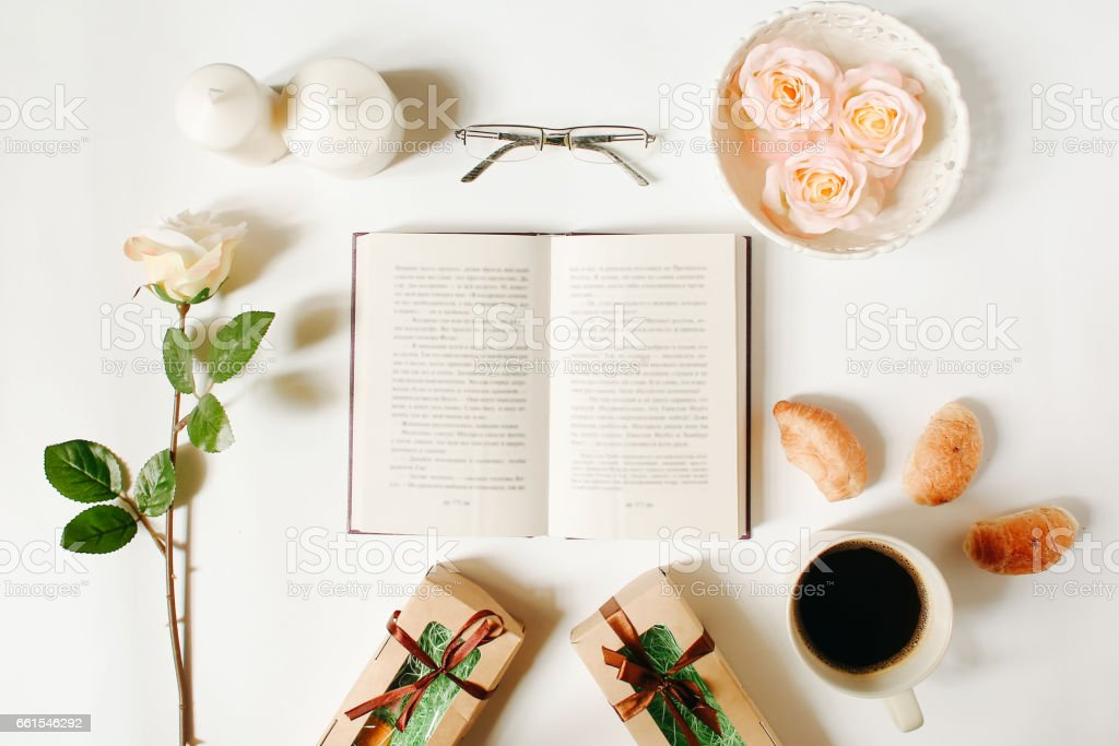 Opened book, glasses, roses, vintage tray, gifts and coffee cup on...