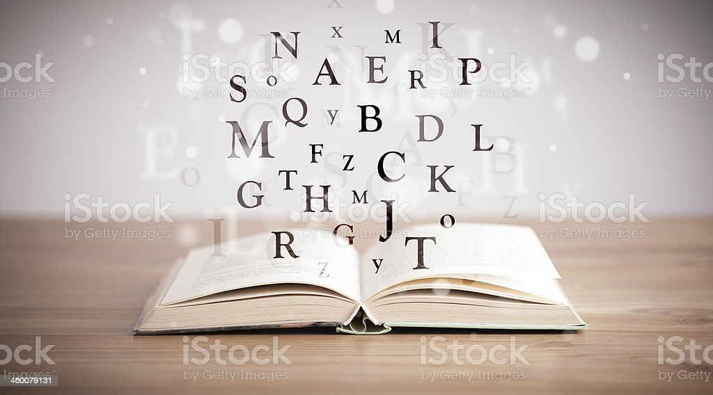 Opened book with flying letters stock photo