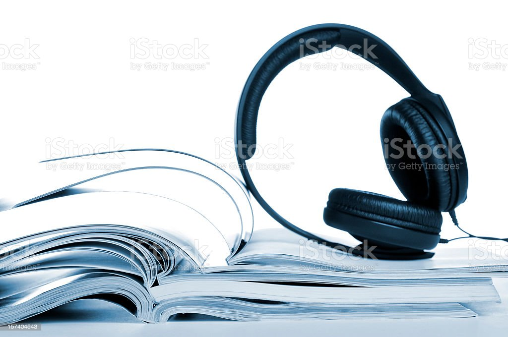 Opened books with headphones lying on them, audio-book stock photo
