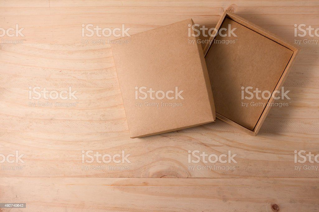 Opened cardboard box on wooden background stock photo