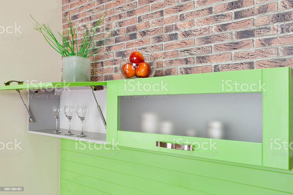 opened cupboard with kitchenware inside of green kitchen stock photo