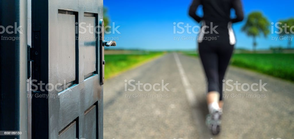 Opened door concept to woman running on a country road stock photo