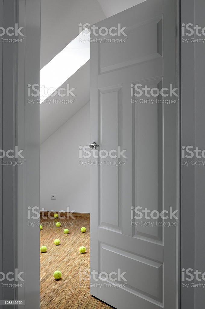 Opened door to the room full of scattered tennis balls stock photo