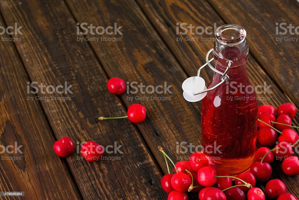 Opened glass bottle with fruit lemonade among several cherries stock photo
