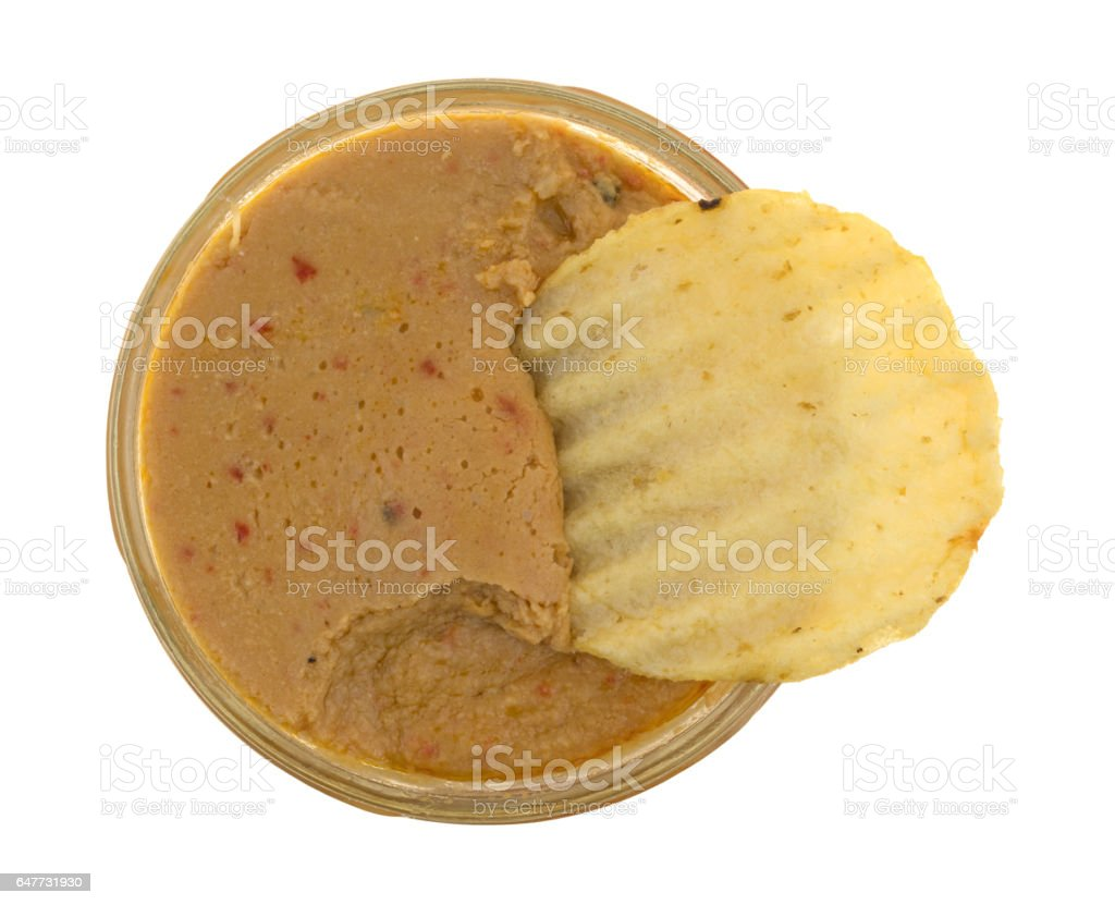 Opened jar of hummus dip with a potato chip stock photo