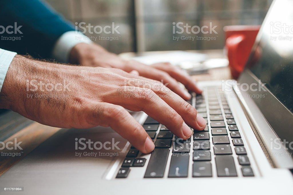 Opened laptop and male hands typing stock photo