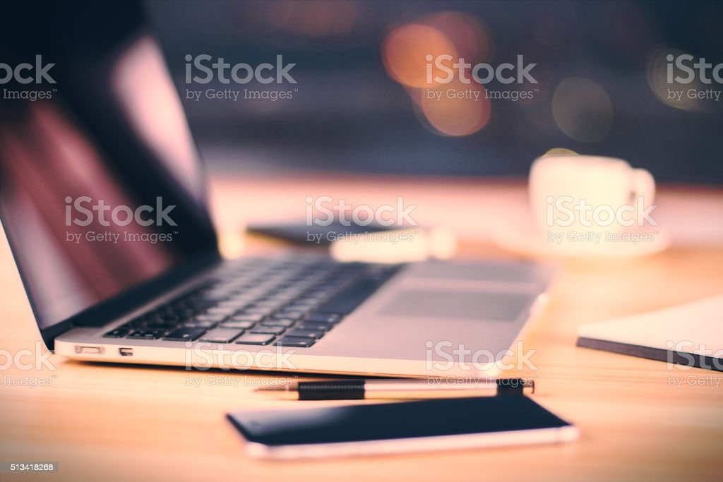Opened laptop, cell phone, cup of coffee and pen stock photo