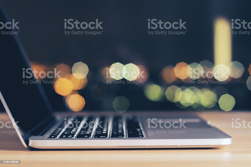Opened laptop on wooden table at night stock photo