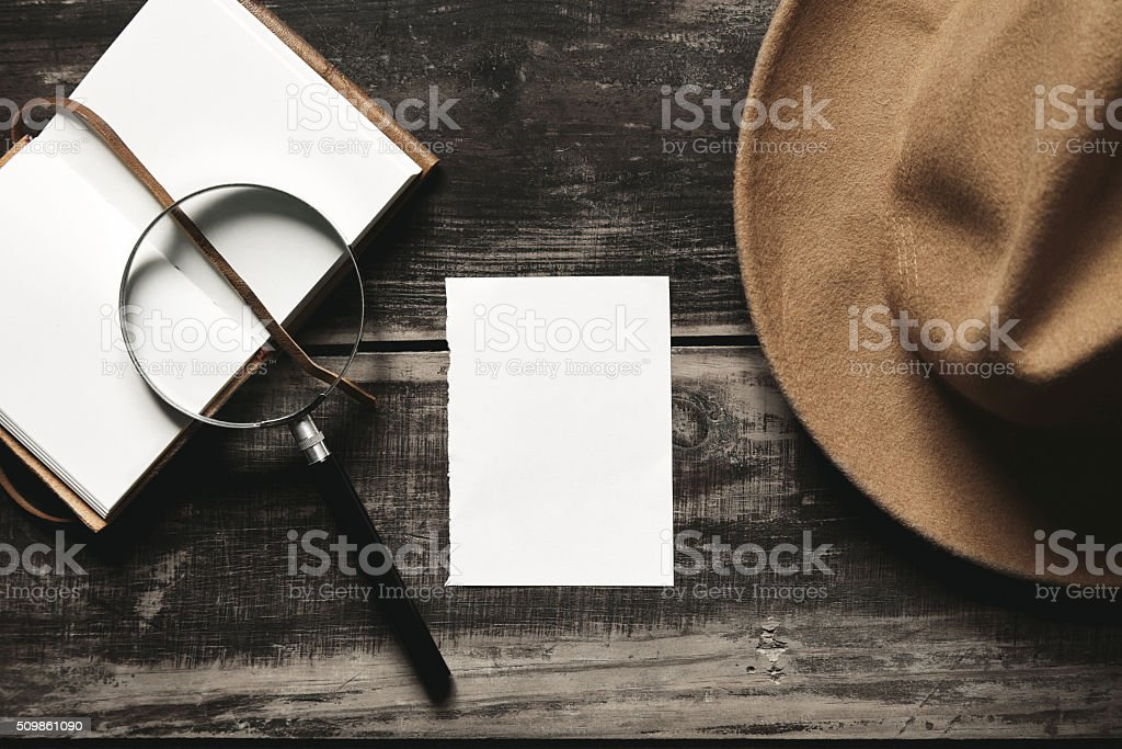 Opened notepok, hat, magnifier paper on black table top stock photo