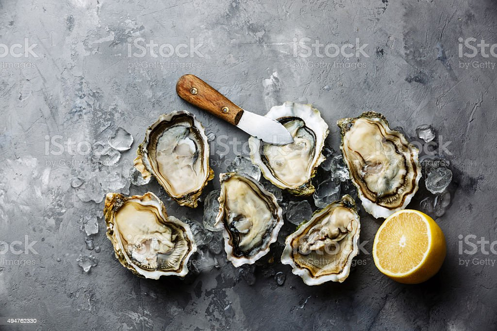Opened Oysters Fines de Claire and lemon stock photo