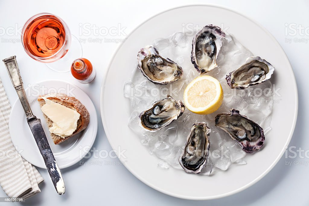 Opened Oysters on white plate stock photo