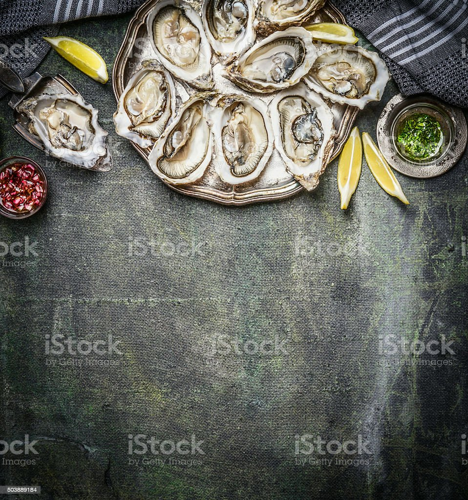 Opened oysters with lemon on rustic background, top view stock photo