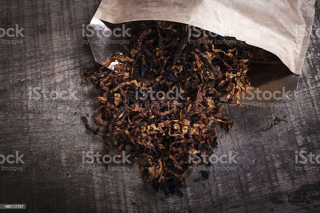 opened package of tobacco on  wooden surface stock photo