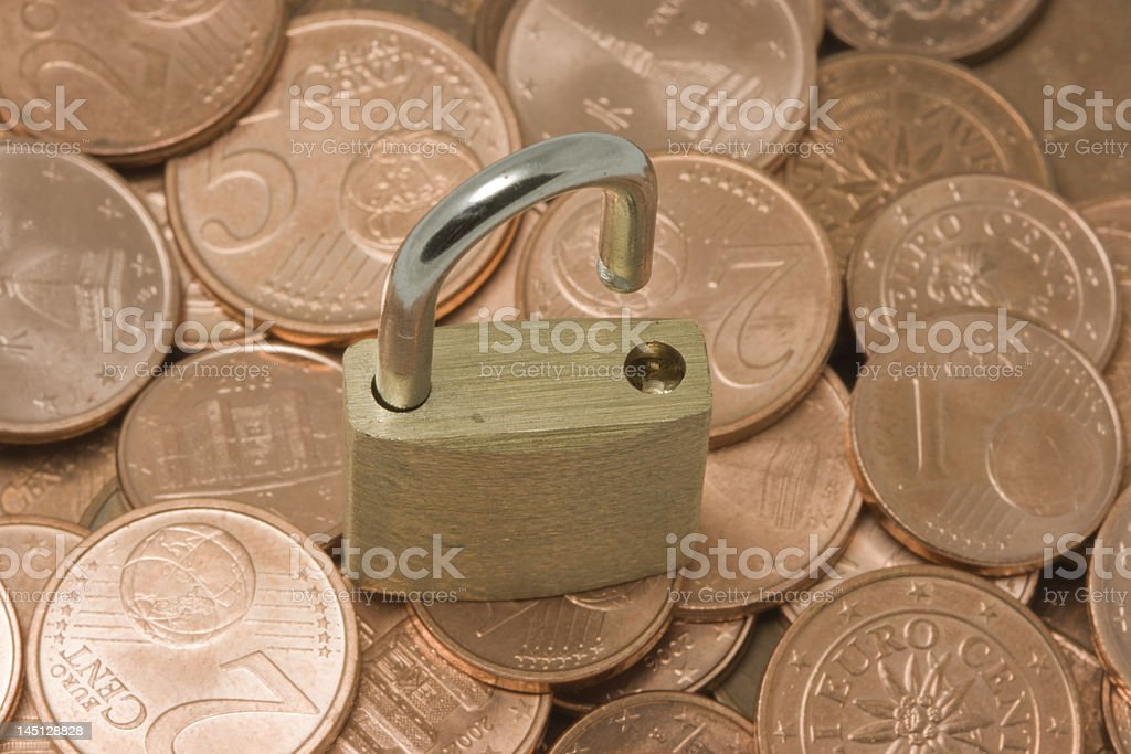 Opened padlock on top of coins pile royalty-free stock photo