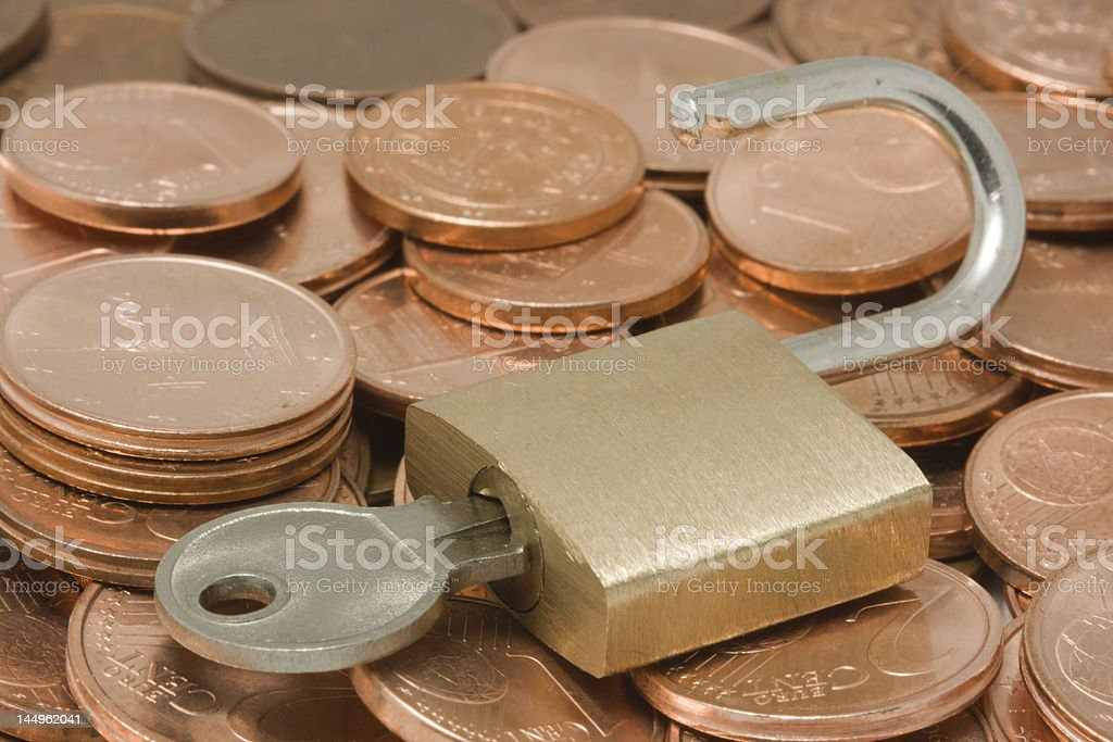 Opened padlock with key on top of coins royalty-free stock photo