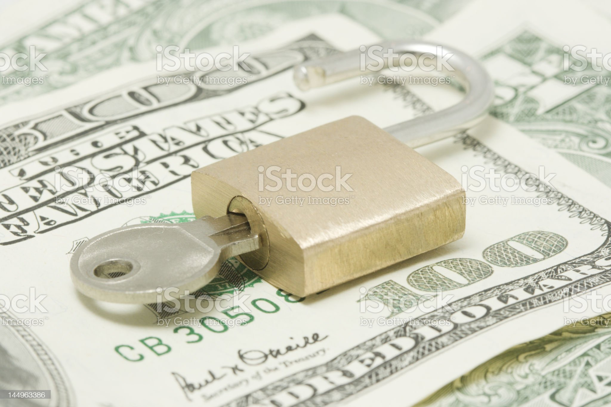 Opened padlock with key on top of hundred dollars bill royalty-free stock photo