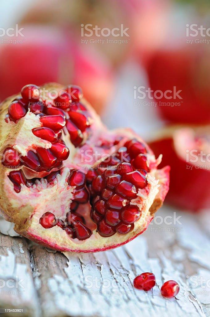 Opened pomegranates on rustic wood background stock photo