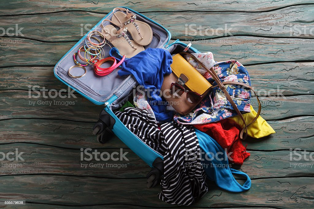 Opened suitcase with crumpled clothes. stock photo