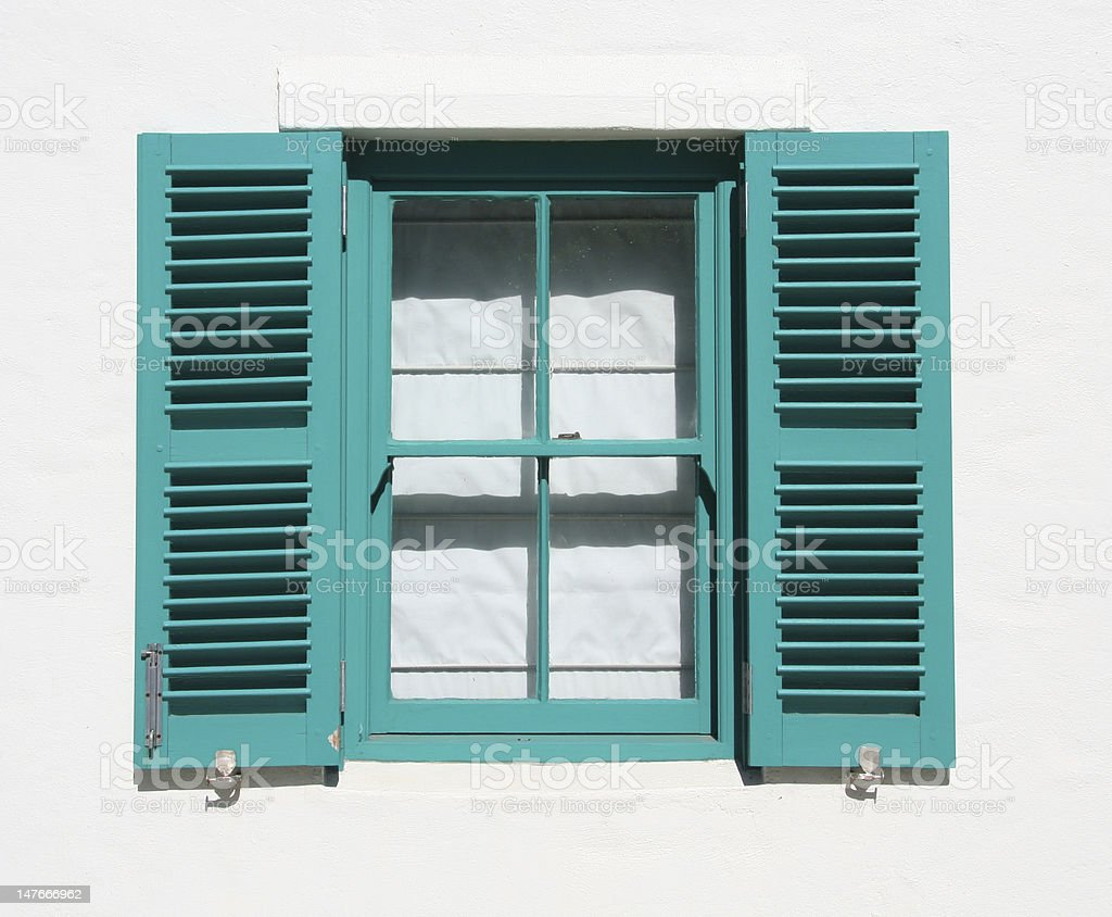 Opened turquoise wooden window on a white house royalty-free stock photo