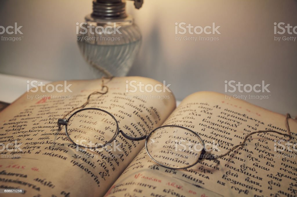 Opened vintage book with old eyeglasses stock photo