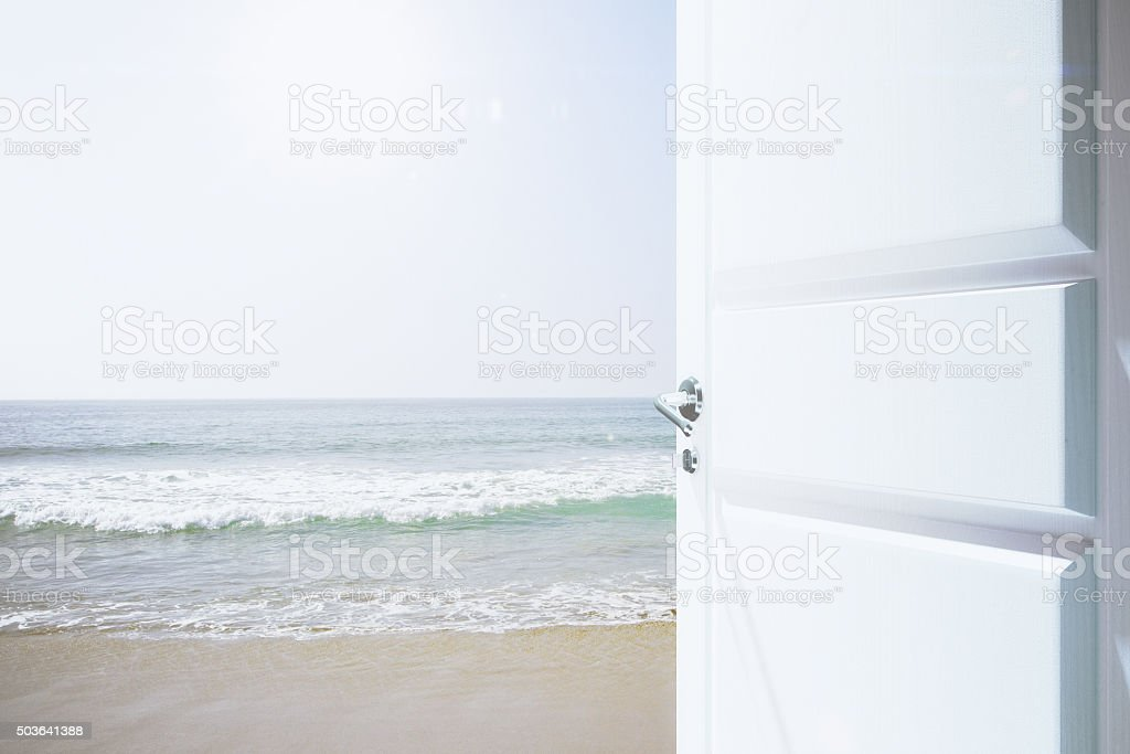 Opened white door to a beachway with ocean stock photo