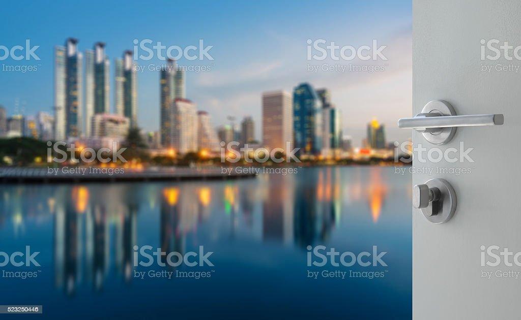opened white door to bangkok city downtown at twilight stock photo