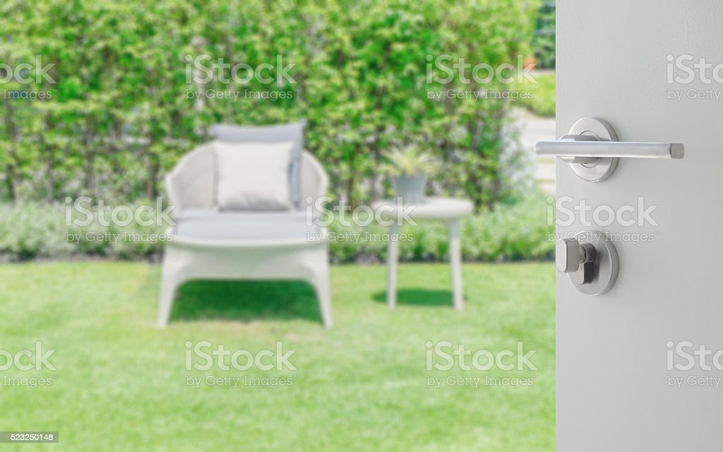 opened white door to blurred white bench in the garden stock photo