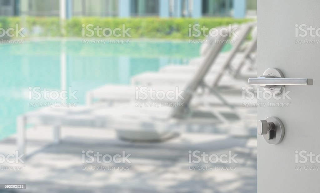opened white door to swimming pool with beach chairs stock photo