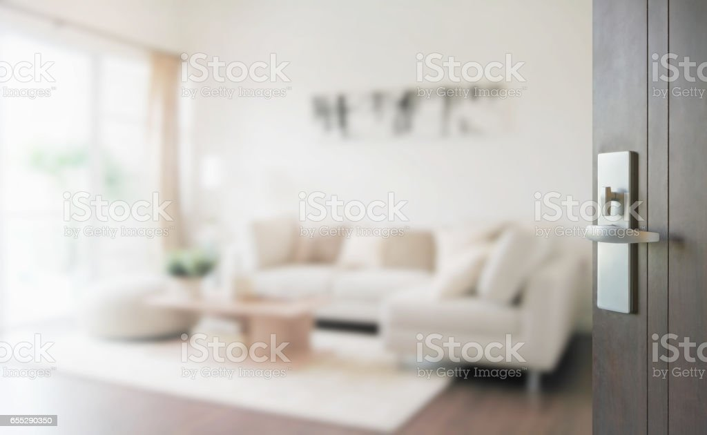 opened wooden door to modern living room interior stock photo