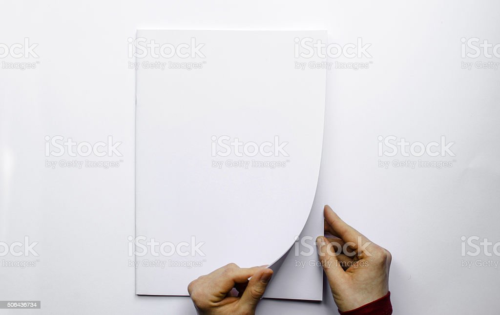 Opening a blank brochure photographed from above stock photo