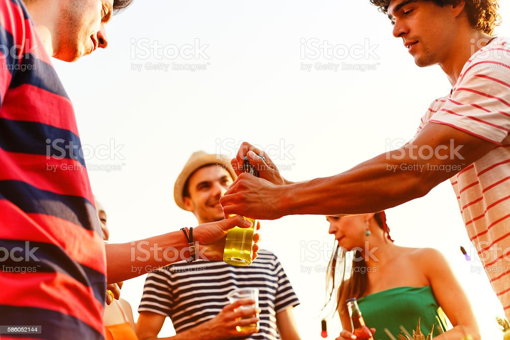 Opening a bottle of beer during party stock photo