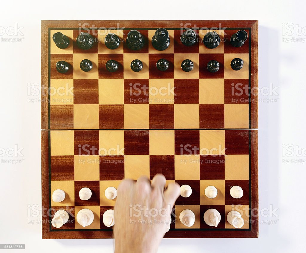 Opening gambit: hand making first move in chess game stock photo