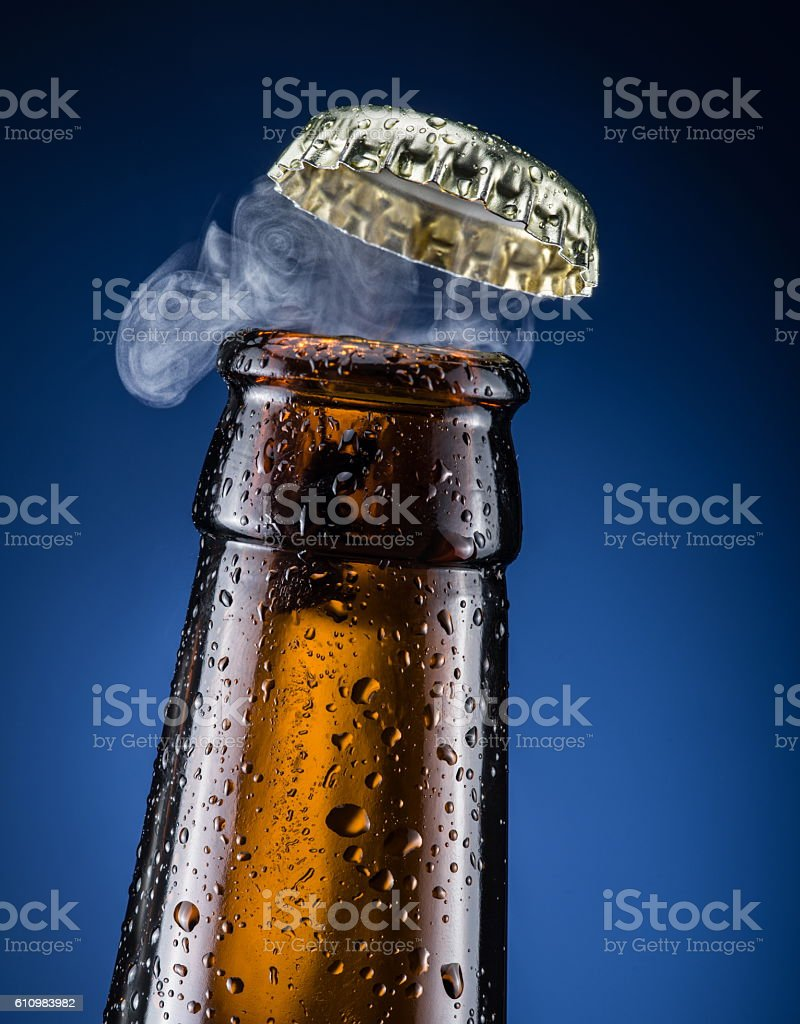 Opening of beer cap with the gas output. stock photo